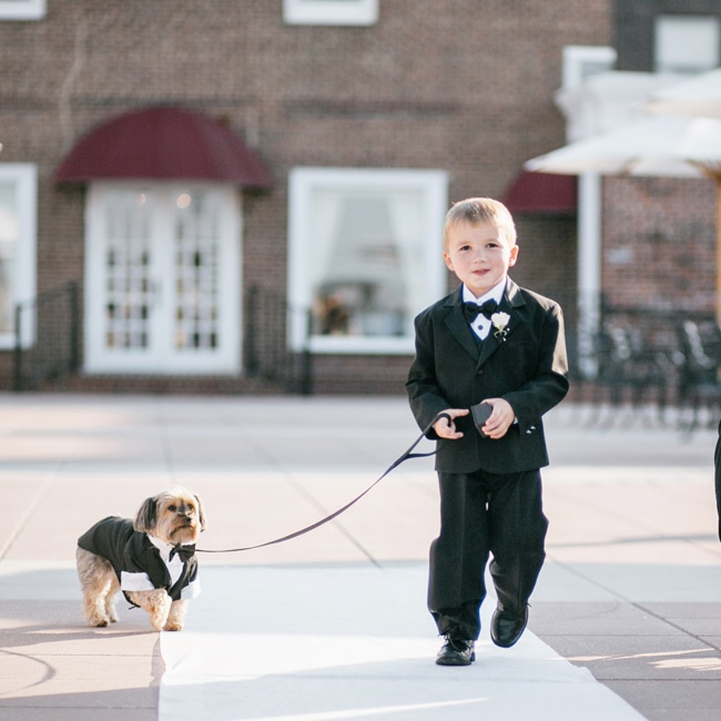 "The ring bearer, dressed in a smart black tuxedo, walked Ashley and Gabby's dog ""Spicy"" down the aisle."