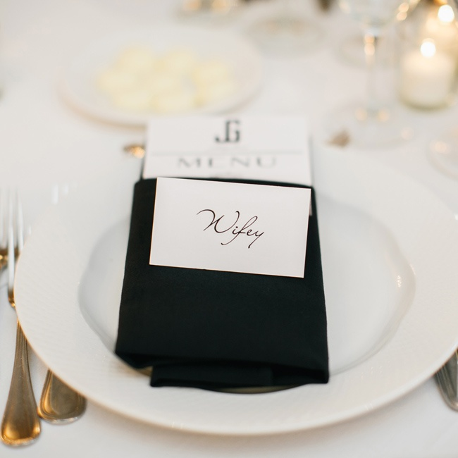 The menus were tucked into black linens and placed on white china. Place cards with elegant script typeface were placed on top of each napkin.