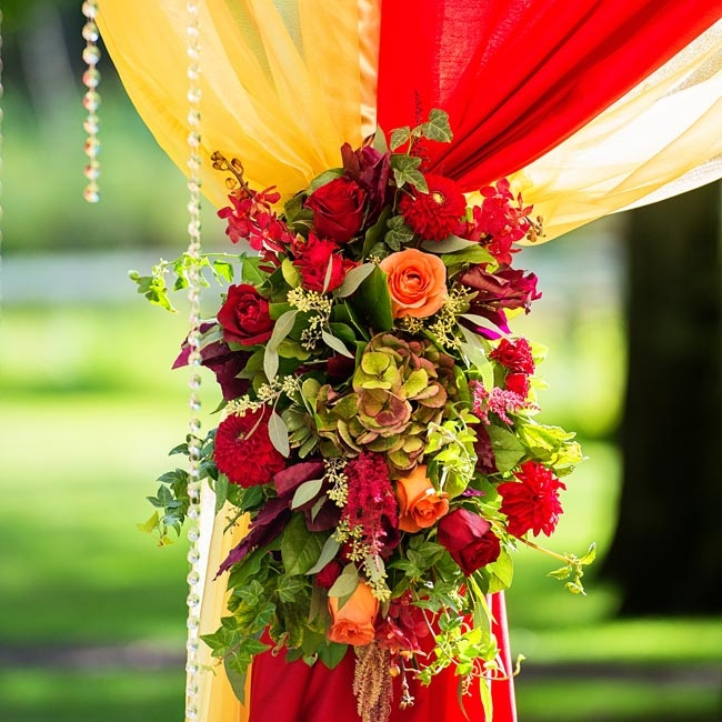 The lavish huppah was decorated with bunches of deep red and peach colored blooms like roses, dahlias, mokaro orchids, amaranthus and hydrangeas.