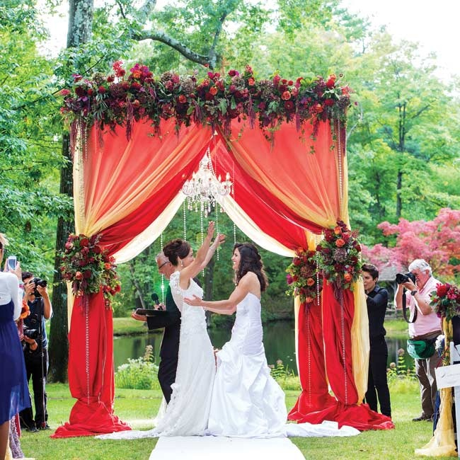A Touch of Elegance custom built Carla and Margaret's huppah. The extravagant huppah was draped with airy red and gold organza fabric and decorated with a lush floral garland. A crystal chandelier hung from the center of the structure of an elegant, glam touch.