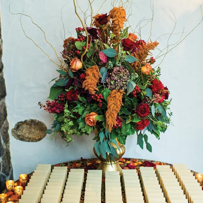 The escort card display was given an elegant, rustic edge with a lush arrangement of roses, hydrangeas, hypernicum berries, seeded eucalyptus and willow branches in shades of deep red, orange and peach.
