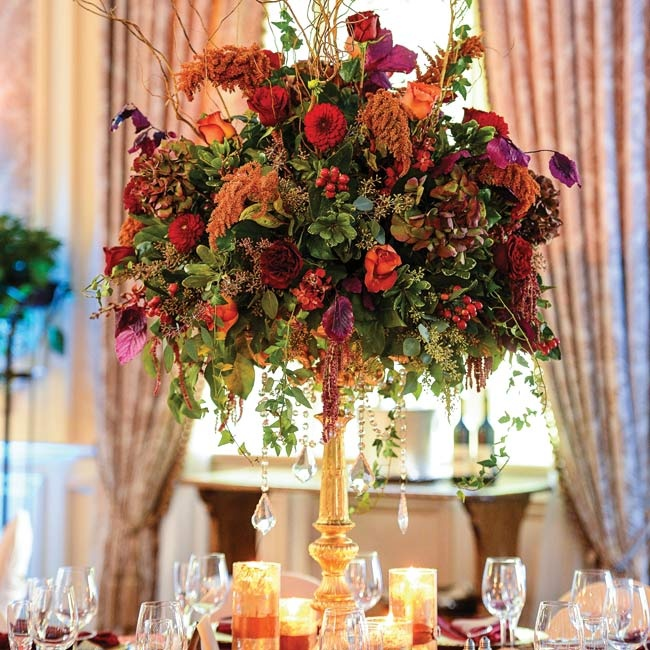 Elegant, autumnal centerpieces composed of roses, astilbe, dahlias, hyperncium berries, seeded eucalyptus and willow branches in deep shades of red and orange were arranged on gilded pedestal vases for a formal look.
