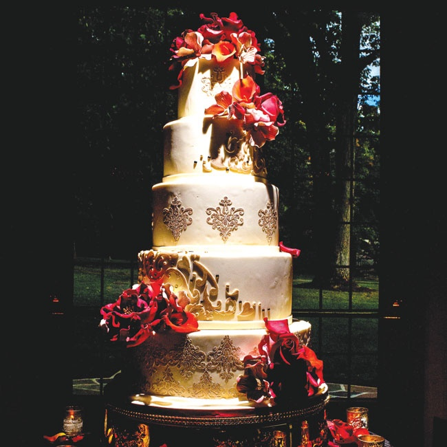 The wedding cake included five extravagantly decorated tiers. Ivory fondant was embellished with edible gold and crystal rococo designs and covered with vibrant red and orange sugar flowers.