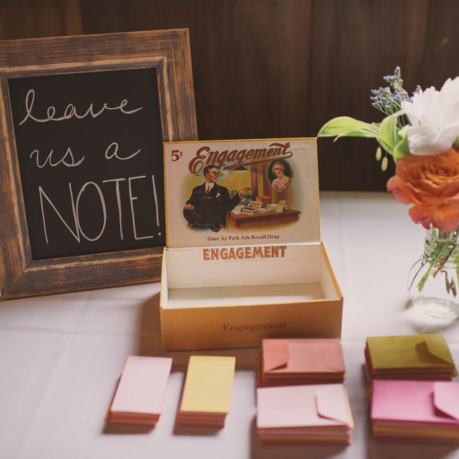The couple encouraged guests to leave them notes in colorful envelopes and place them in a vintage engagement-themed cigar box.