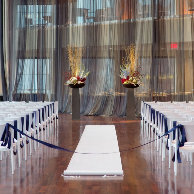 White chairs, waxed wooden floors, white aisle runners and striking floral arrangements made up the preppy indoor ceremony decor.