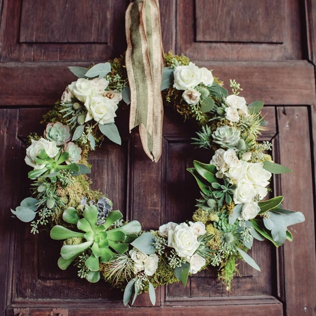 A rustic wreath, made of succulents, white roses and lots of greenery, hung on one of the doors at The Wild Onion Ranch.