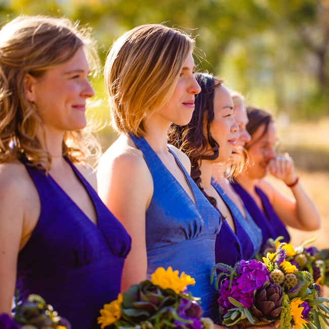 Bridesmaids wore blue V-neck dresses and carried bouquets of sunflowers, kale and scabiosa pods.