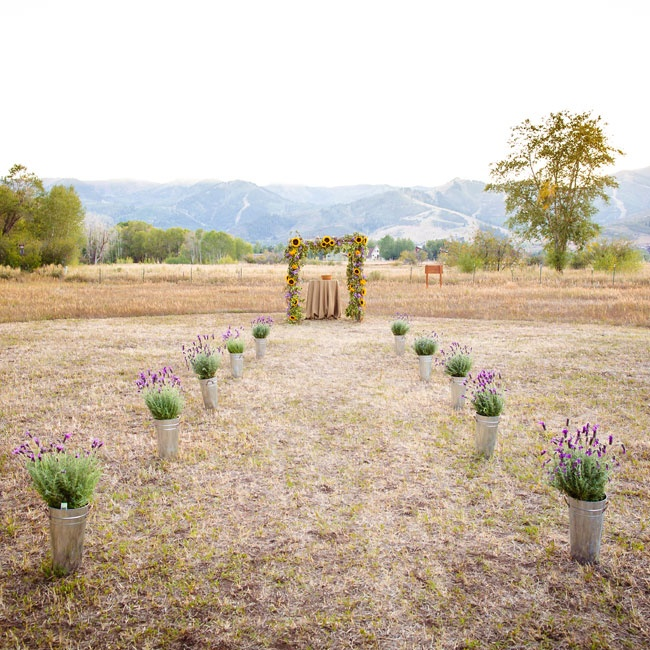 The rustic ceremony aisle was lined with lavender pots and the centerpiece was a floral ceremony arch filled with sunflowers and lavender.