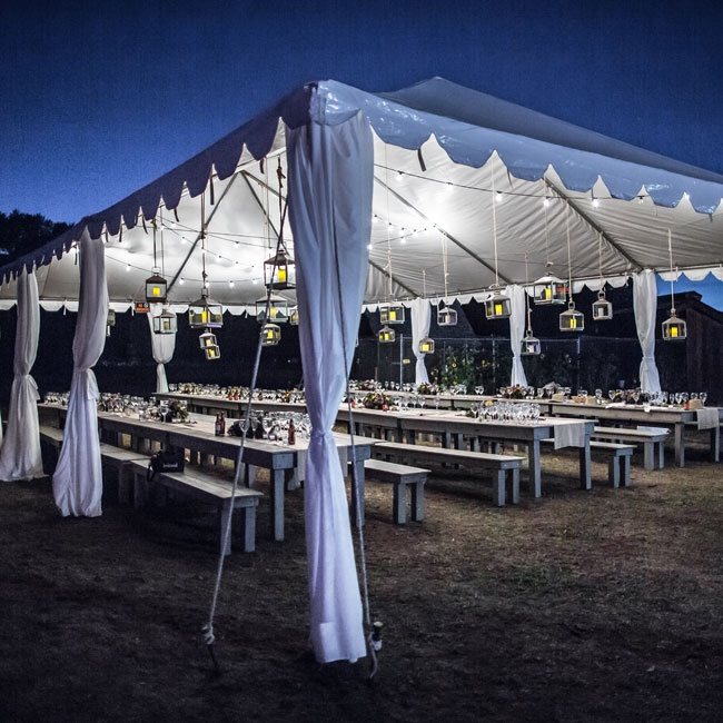 Guests ate family-style at long farm tables beneath an impressive tent with hanging lanterns.