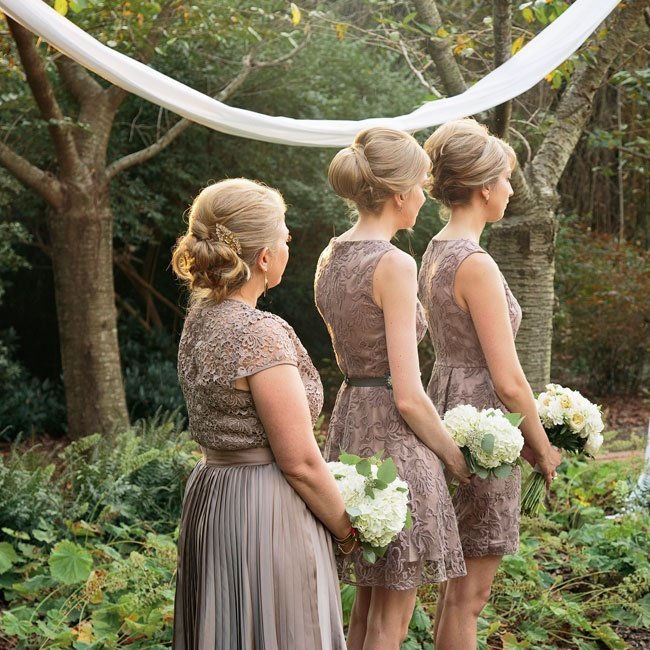 The bridesmaids wore matching embroidered lace gowns in a soft shade of dusty purple, while the maid of honor wore a embroidered lace top with a pleated skirt in the same purple hue.