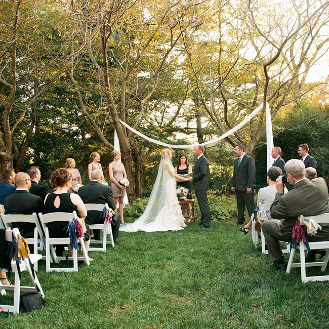 The couple gathered with family and friends for a simple outdoor ceremony. In lieu of a traditional wedding arch, the couple draped airy white fabric between two trees.