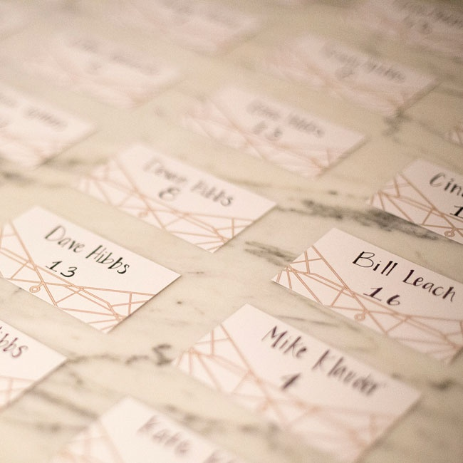 The name of each guest and their table were hand calligraphed onto the escort cards, along with a gold Art Deco-inspired design.