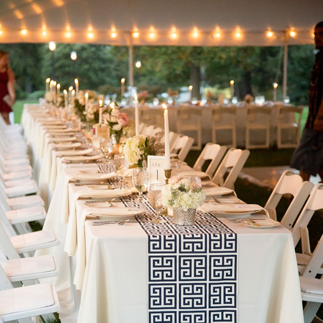 Long farm tables were set with ivory linens, blue and white Greek key pattern table runners and gold accents for an Art Deco-inspired look.  Golden candlesticks with long white candles added a formal, elegant touch to the tablescapes.