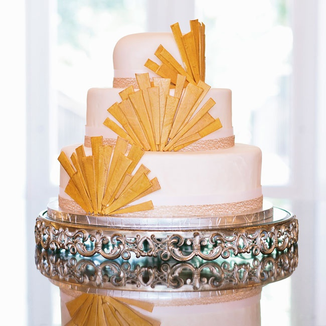 Laura's sister made the couple's three-tier Art Deco-inspired cake. Each layer was covered in ivory fondant and a gold fan detail.