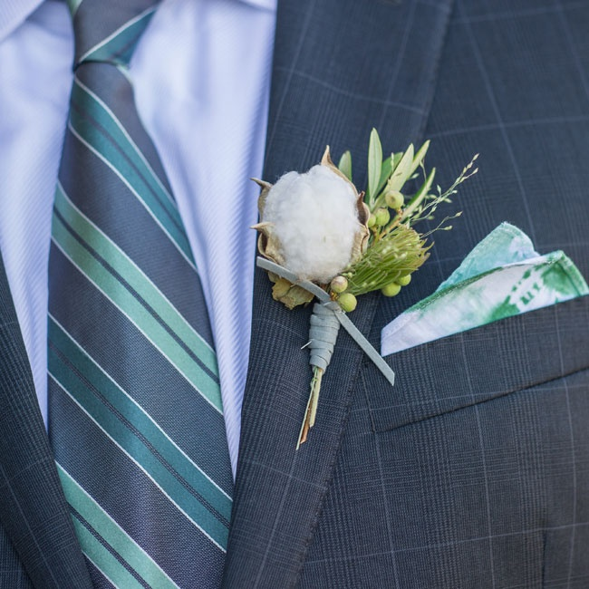 The groom's boutonniere featured a large cotton bloom with textured green accent plants.
