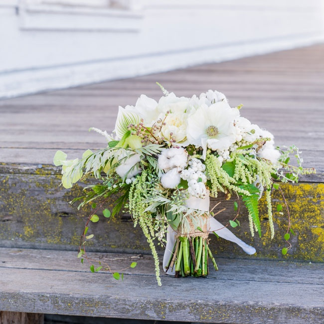 The bride's bouquet was full of white blooms, including balls of cotton, anemones, peonies and hypernicum berries.