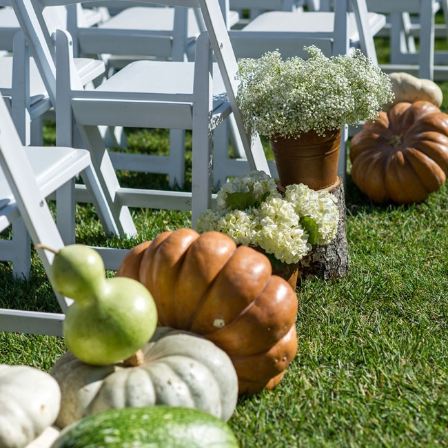 Pumpkins and squash in various sizes, shapes and colors lined the ceremony aisle.