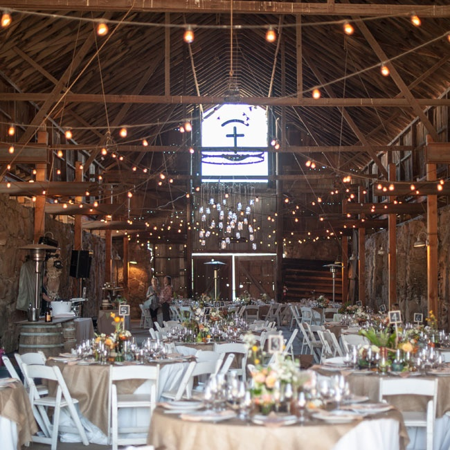 A large barn hall was decorated in cafe lights and set up with round reception tables in neutral linens.