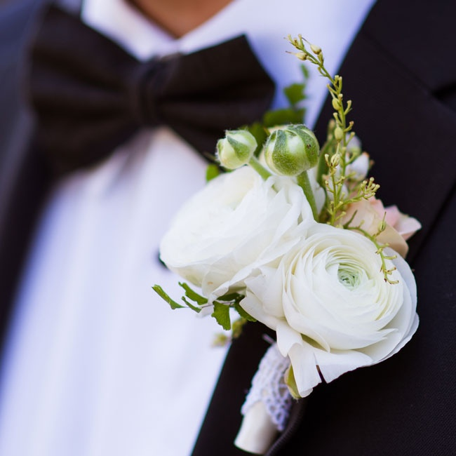 The groom accessorized his traditional tux with a white ranunculus boutonniere.