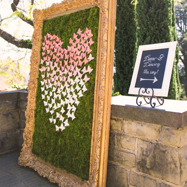 A selection of ombre pink and white butterflies were arranged in a heart shape on a bed of moss in a gigantic gilded frame as escort cards.