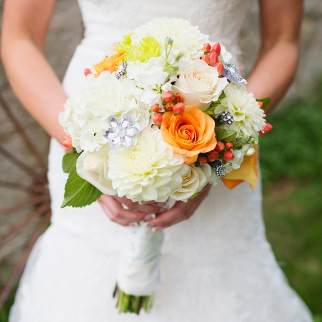 Dahlias, roses and hypernicum berries filled Carries bridal bouquet in vibrant orange and pure white color.