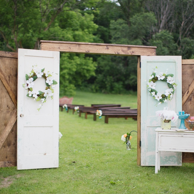 Guests walked through these artful free-standing doors accented with fresh flower wreaths at the outdoor ceremony.