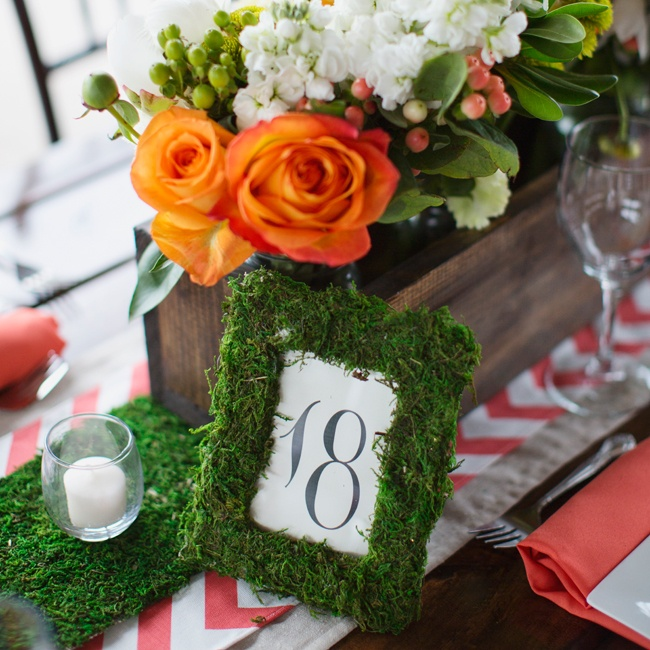 Table numbers were lined in moss next to wooden boxes of orange roses and white and pink hypernicum berries.