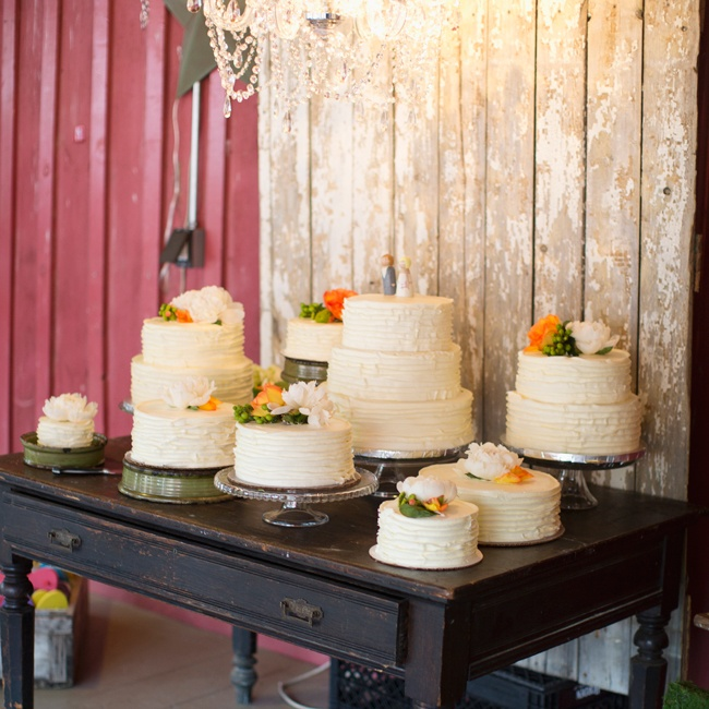 An array of cakes in various sizes and heights were artfully arranged on a wooden table and topped with fresh flowers in orange and white.