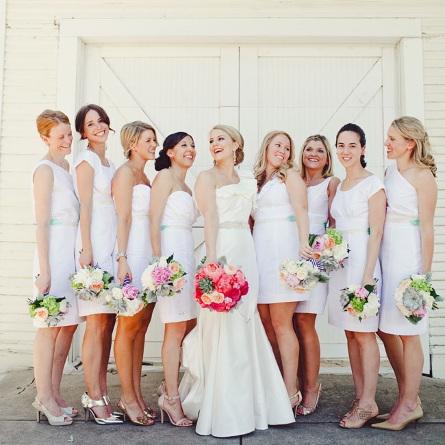 "Sarah's eight bridesmaids wore custom white dresses in the style of their choice. ""We jazzed them up with a mint sash and neon pink earrings,"" Sarah says. ""I'm sure some people were horrified by the idea of the bridesmaid dresses matching the bride, but they looked so gorgeous!"""