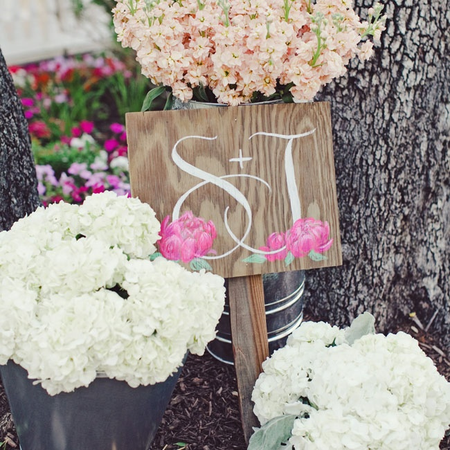Rustic buckets filled with hydrangeas and stock sat next to a hand-painted sign with the couple's initials on it.