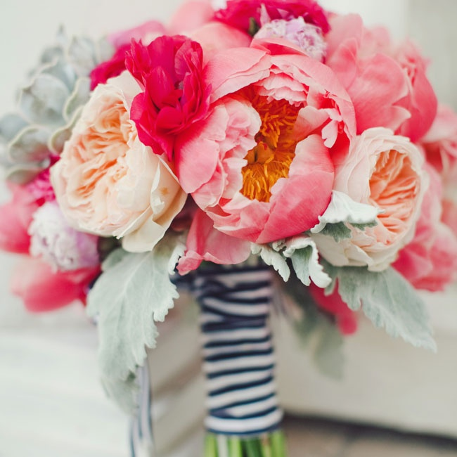 Striped ribbon was tied around the stems of the lush peonies, garden roses and ranunculuses in the bride's bouquet.
