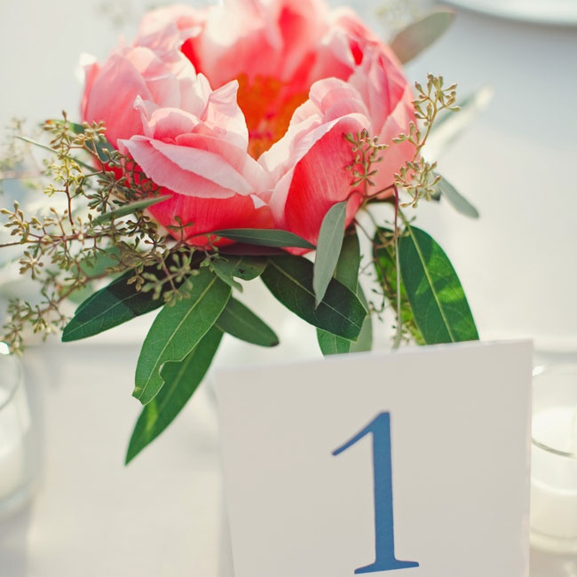 "Simple table numbers sat next to laid-back arrangements of peonies and seeded eucalyptus. ""Since we had a family-style dinner, Posey created a collection of beautiful centerpieces that didn't overwhelm the tables,"" says Sarah."
