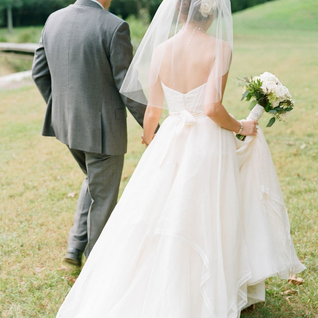 Lauren wore a classic A-Line gown by Watters. The strapless dress had layers of asymmetrically cut organza and a simple ivory ribbon at the waist. For the ceremony she wore a simple elbow length veil.
