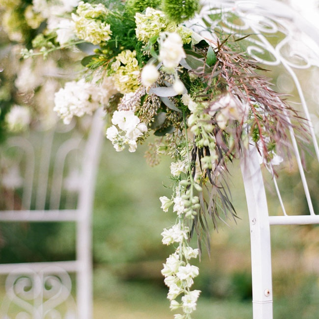 The simple wedding arch was draped with a lush floral garland with hydrangeas, stock flowers eucalyptus and grasses for a understated, rustic look.
