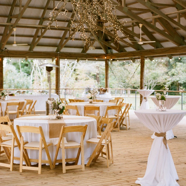 The reception was held in the open air pavilion at the Hilltop Arboretum. The tables were covered in simple white linens, burlap table runners and understated floral arrangements in pewter jugs. A willow branch light feature added a whimsical, woodland touch to the space.