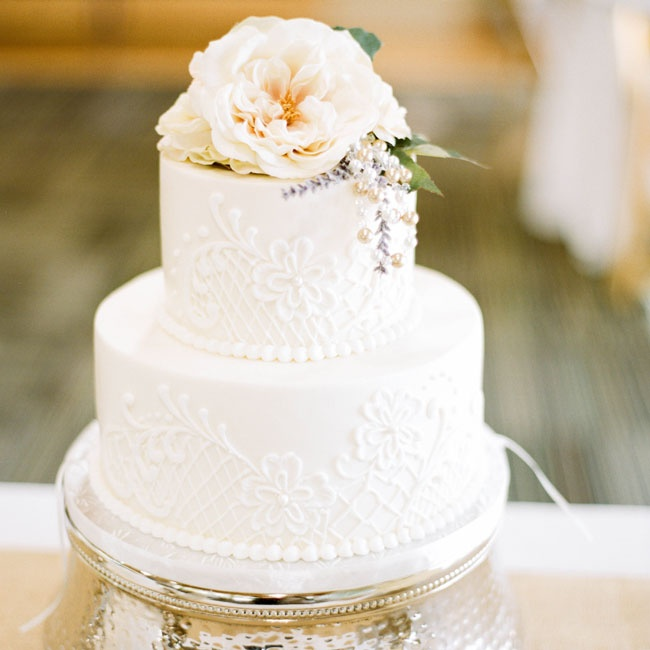 The couple's two tier fondant cake was decorated with floral and lattice embroidery, buttercream pearls and topped with ivory lisianthuses and sprigs of lavender.