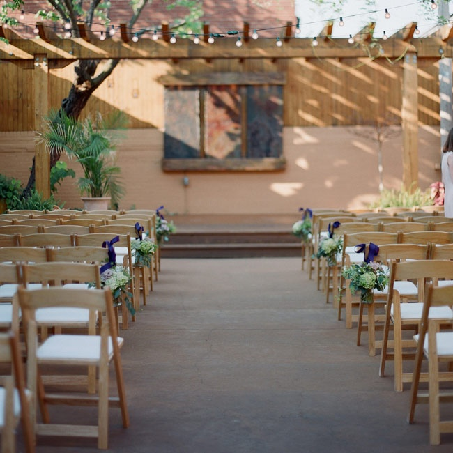 The couple exchanged vows in a small courtyard beneath a pergola. Mason jars filled with hydrangeas, ornamental kale, ferns and lavender roses decorated the ends of the guest chairs along the aisle.