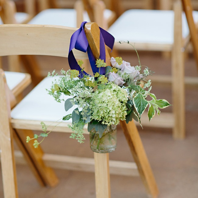 Hanging from the ceremony chairs were jars of green hydrangeas, purple ornamental kale, fern, lavenders roses and seeded eucalyptus.