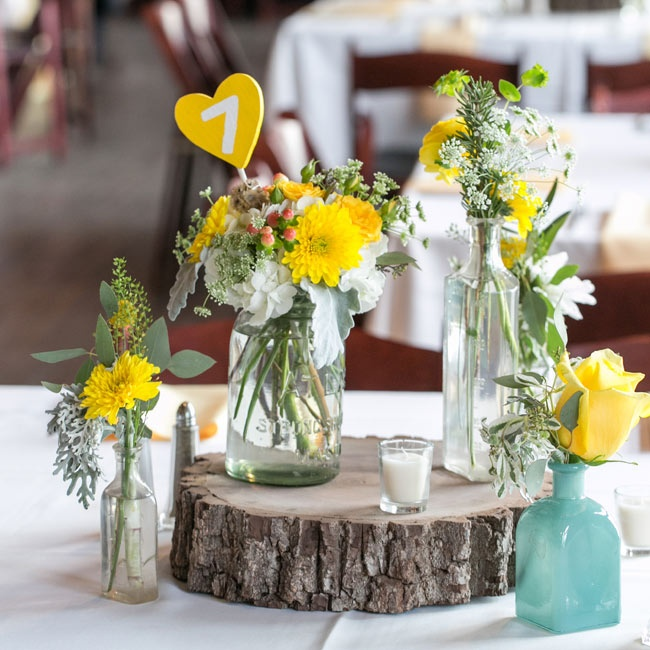 Small bottles filled with bright arrangements of dahlias, baby's breath, and roses sat a top wooden tree slices, adding a charming and rustic vibe to the table decor.