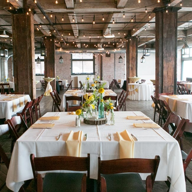 The couple let the historic charm of The Hobbs Building take center stage, and kept the decorations to a minimum using white tablecloths, low rustic centerpieces, and cafe lights strung across the ceiling.