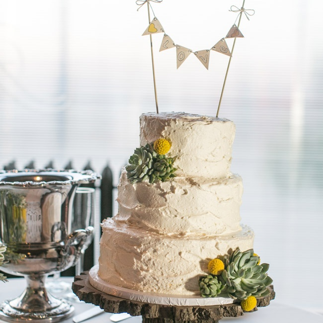 "The couple's white wedding cake featured an adorable paper bunting cake topper that spelled ""love""."