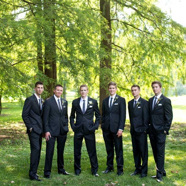The groomsmen wore dark charcoal gray suits paired with charcoal ties and simple white pocket squares.