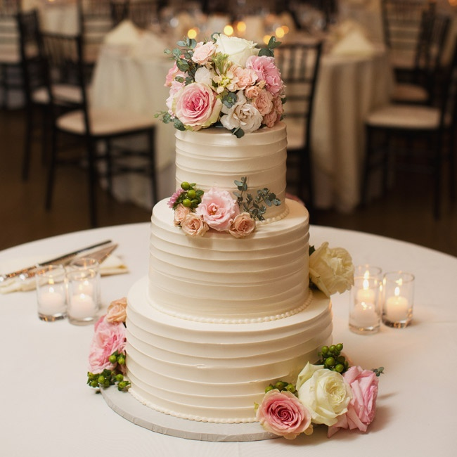 The three-tier buttercream cake was decorated with fresh roses in the same elegant color palette as the rest of the wedding.