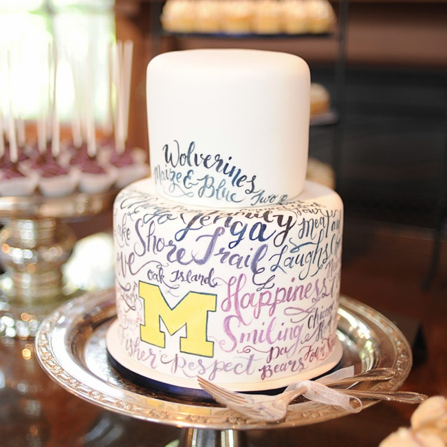The wedding cake was a two-tier white cake with University of Michigan-themed phrases, hand-painted on the bottom tier.