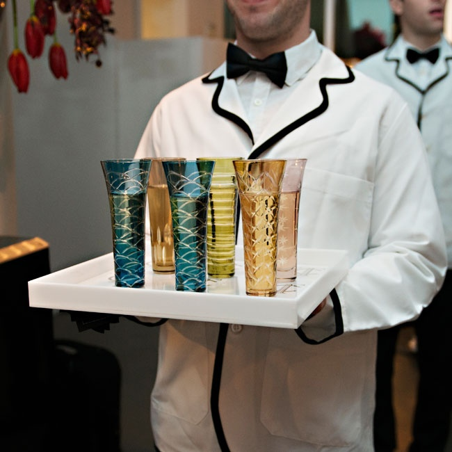 Waiters in white coats trimmed in black carried trays of colorful champagne glasses to guests.