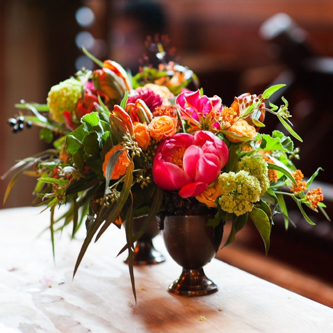 A mix of wildflowers and peonies in pink, green and orange flanked the reception tables.