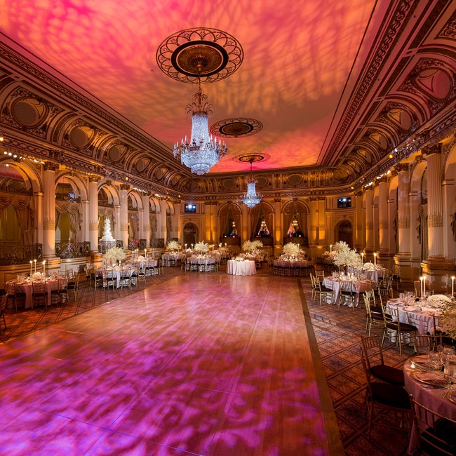Pink and orange spotlights cast a rococo pattern on the dance floor and gave the ballroom a warm romantic glow.