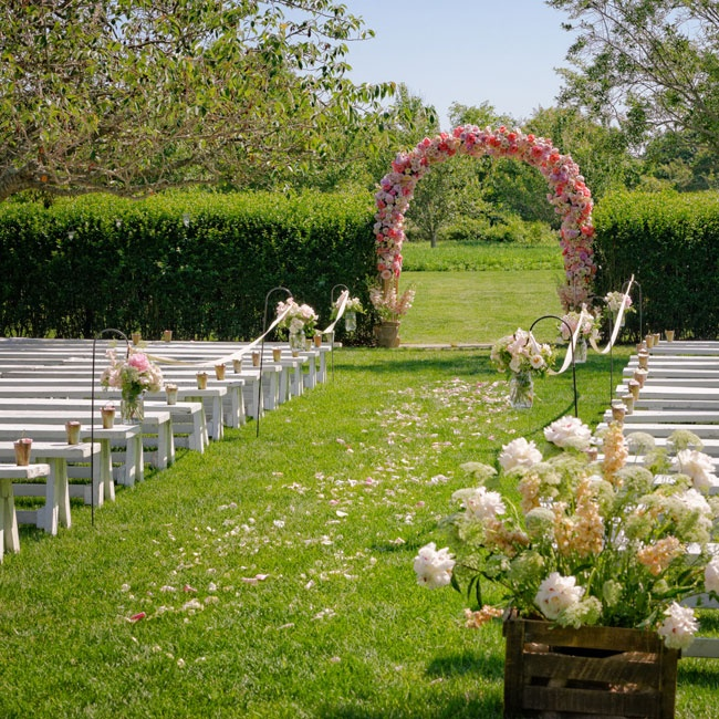 The ceremony was held in a clearing at Kim's parent's home. The aisles were lined with simple white benches and shepherd's hooks holding romantic bunches of white and pink blooms. The couple exchanged vows under a lush floral arch that separated the ceremony from the cocktail hour.