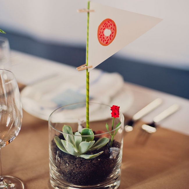 Instead of traditional table numbers, the couple placed illustrated pennant flags in mini terrariums on the tables.