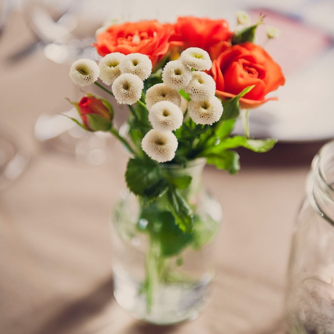 Grace's mother arranged all of the floral centerpieces for the reception using flowers she and Andrea had bought at the flower market earlier that day. Each arrangement was placed in a vintage vase Grace's mother had collected in the months leading up to the wedding.